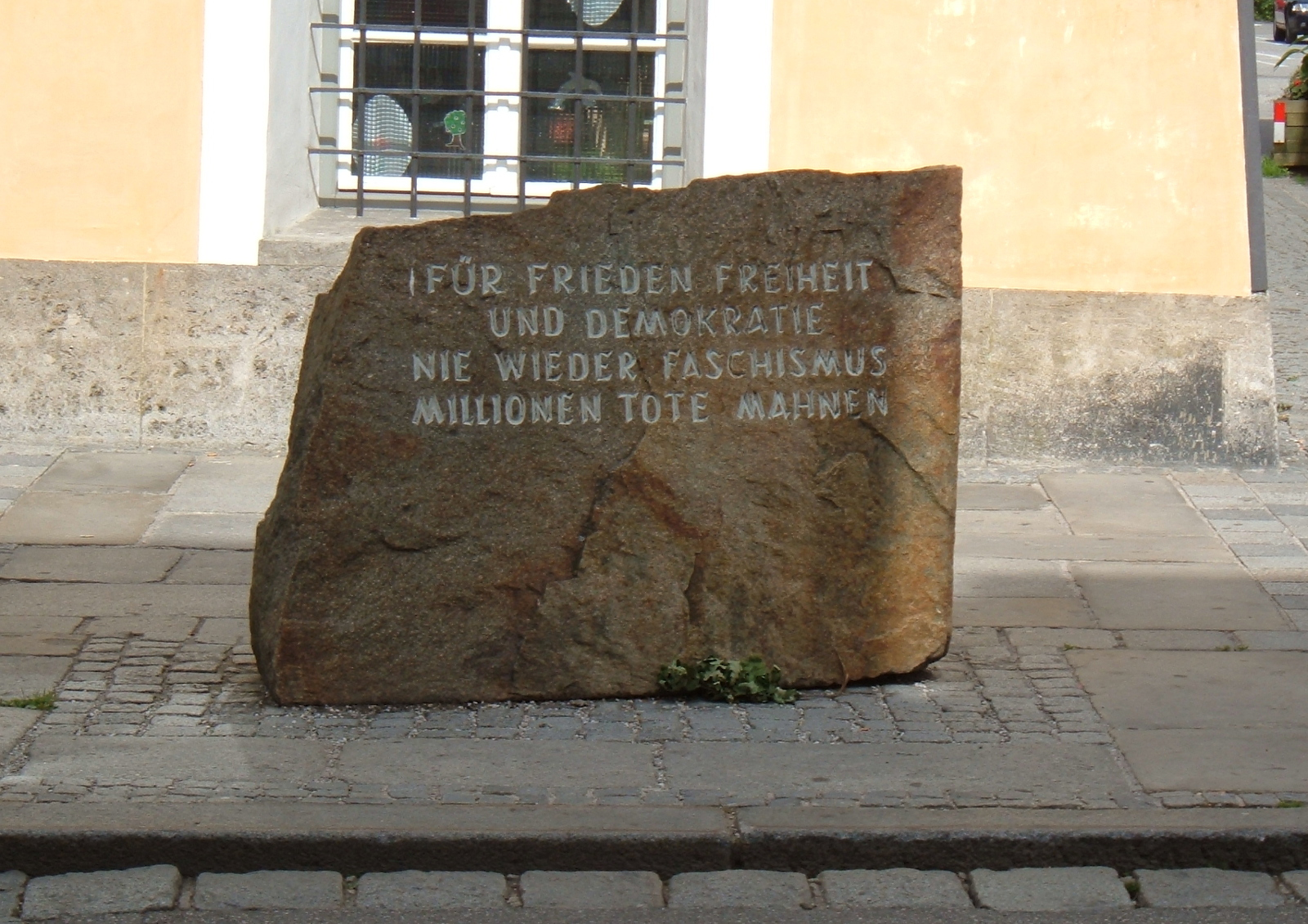 "Monument in front of Hitler's birthplace: ""For peace, freedom, and democracy, never again fascism, millions of dead implore."""
