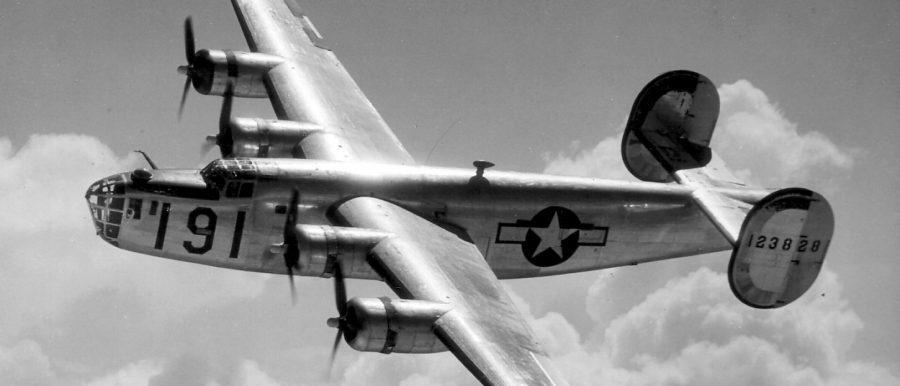 A Consolidated B-24 Liberator from Maxwell Field, Alabama, four engine pilot school, glistens in the sun as it makes a turn at high altitude in the clouds.