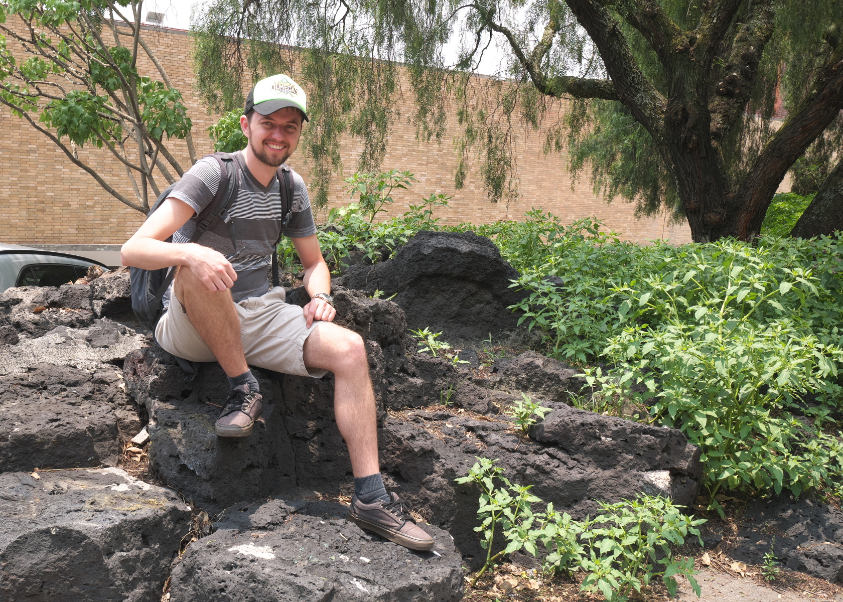 Your blogger sitting on a surviving piece of the Pedregal on the UNAM campus. (Photo by Verónica Trinidad Gallegos.)